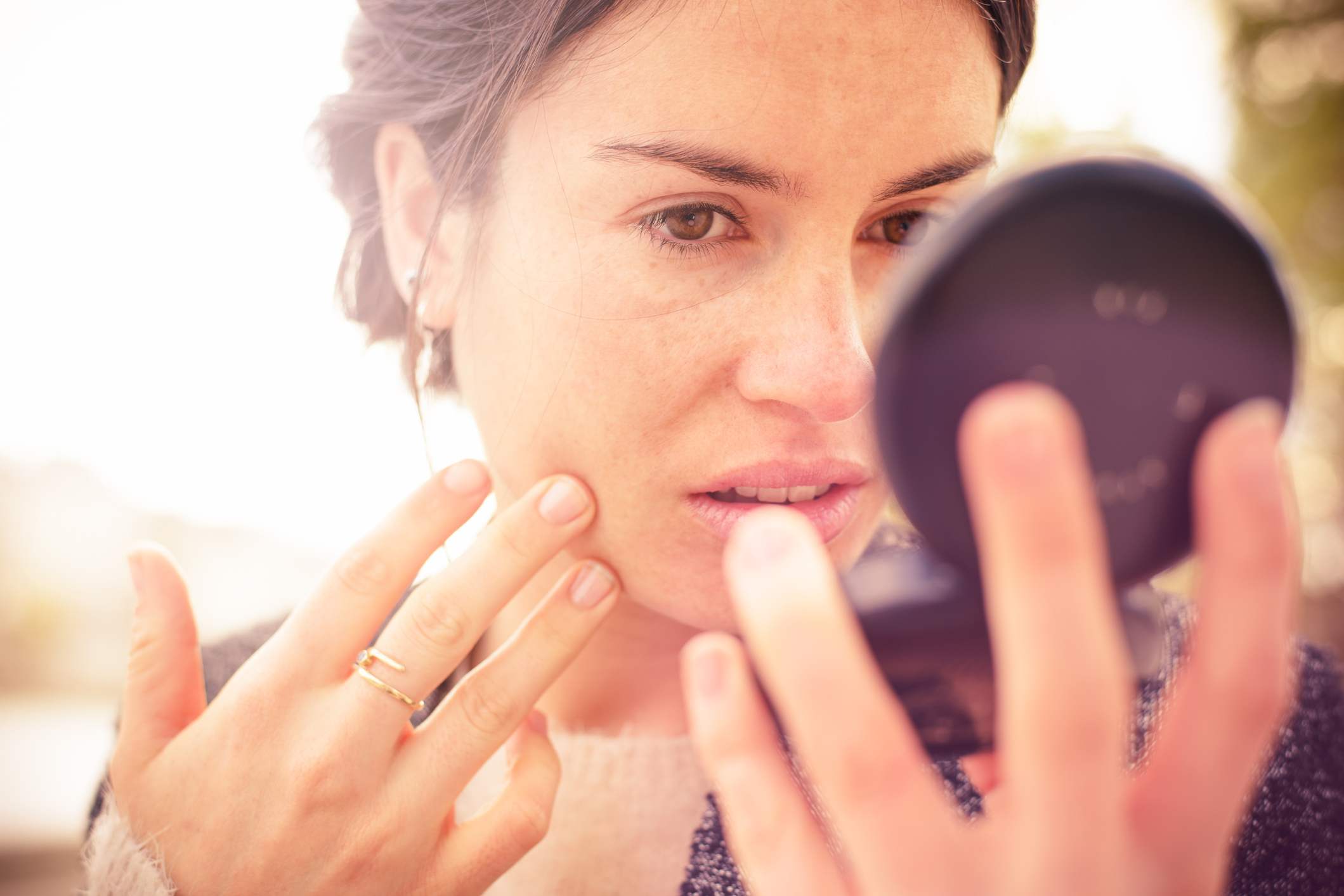 Woman checking appearance in compact mirror