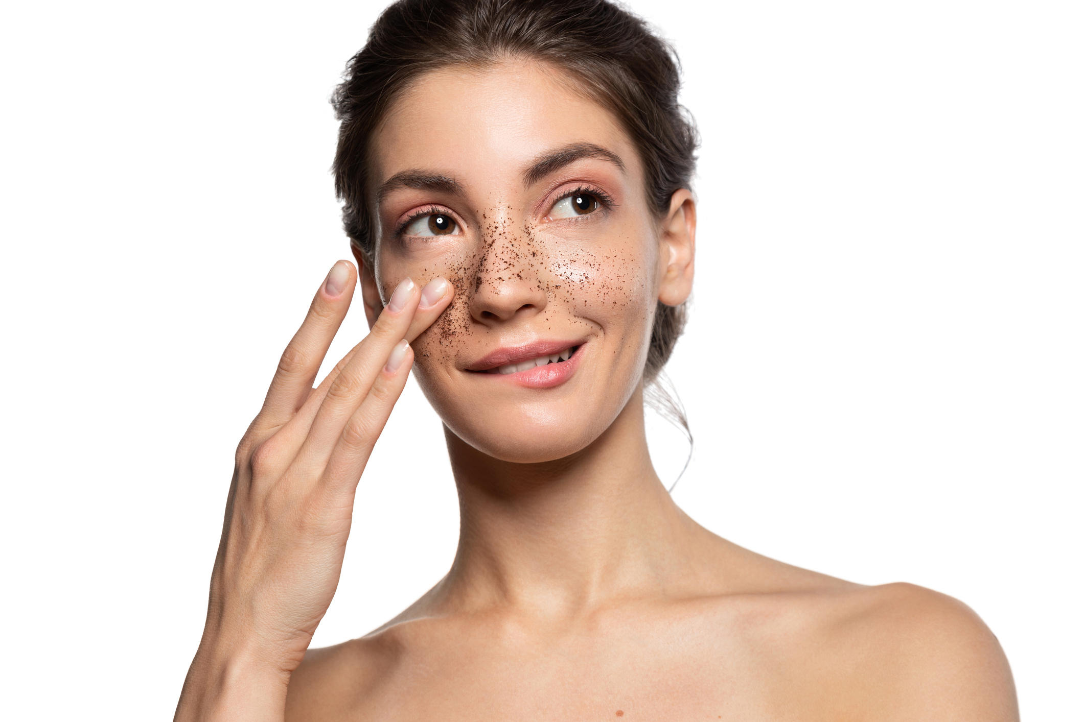 Young woman applying exfoliating scrub to her face